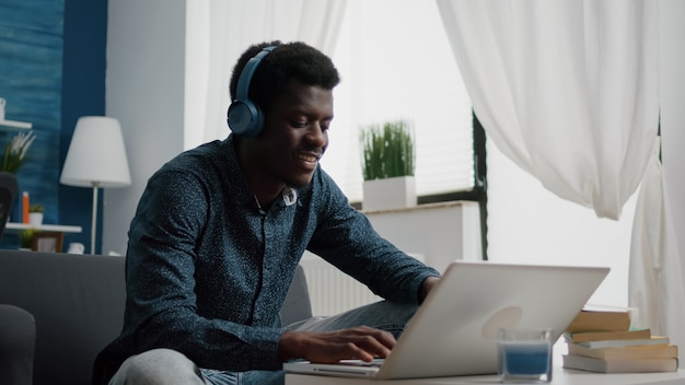 Jonge man met koptelefoon, typen op laptop, met behulp van internet web online services