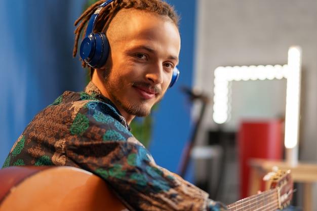 Jonge man met koptelefoon zittend op de bank en gitaar spelen close-up