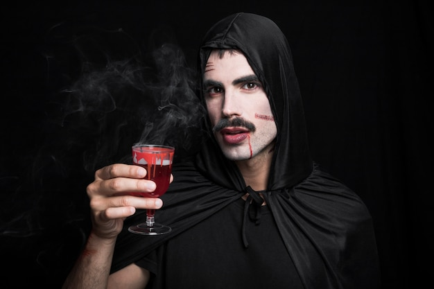 Jonge man met krassen op wit gezicht houden dampende drankje