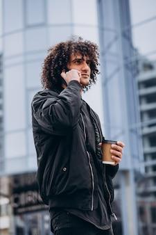 Jonge man met krullend haar koffie drinken en praten aan de telefoon