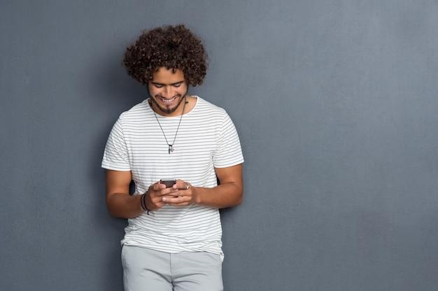 Jonge man met krullend haar, leunend tegen een grijze muur met behulp van mobiele telefoon