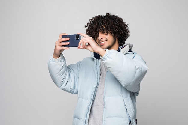 Jonge man met krullend haar met behulp van mobiele telefoon over geïsoleerde witte muur