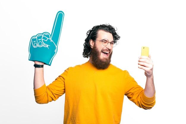 Jonge man met krullende baard is enthousiast over nieuw aan de telefoon, wijst met zijn ventilatorhandschoen.