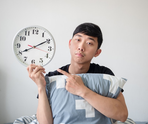 Jonge man met kussenpuntvinger op de klok in de hand en verveeld werk laat concept?