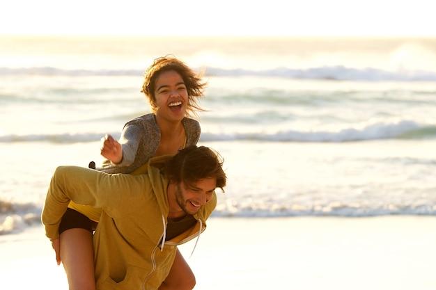 Jonge man met lachende vrouw op terug op het strand