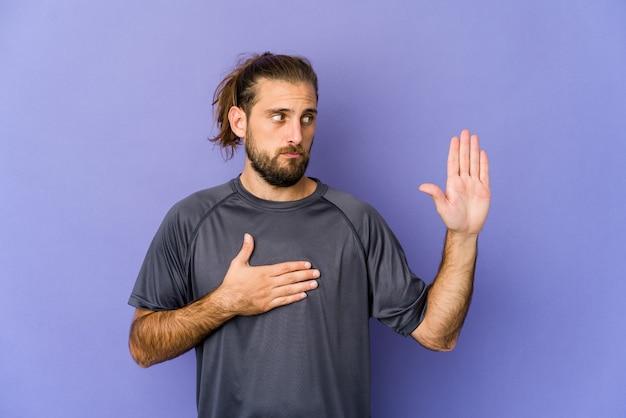 Jonge man met lang haar kijkt een eed af en legt de hand op de borst