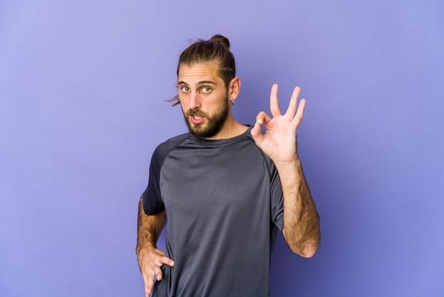 Jonge man met lang haar kijkt een oog dicht en houdt een goed gebaar met de hand.