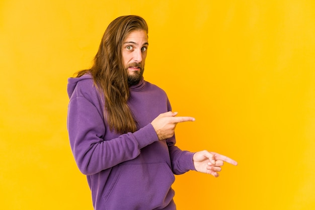 Jonge man met lang haar kijkt geschokt met wijsvingers naar een kopie ruimte
