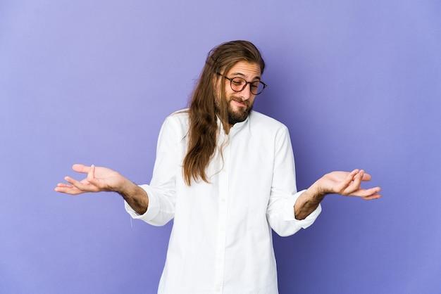 Jonge man met lang haar kijkt twijfelend en haalt schouders op in vragend gebaar.