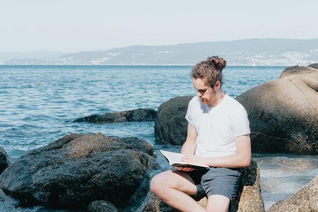 Jonge man met lang haar leest een boek aan de kust van het strand tijdens een heldere dag, kopieer ruimte, ontspan en meditatie concept