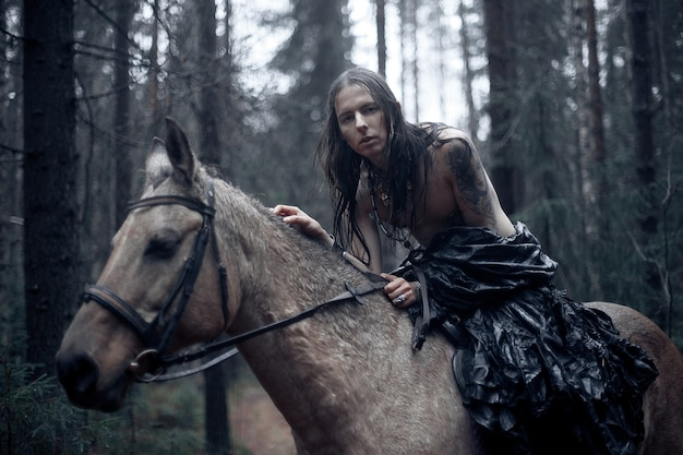 Jonge man met lang haar met paard in donker bos.