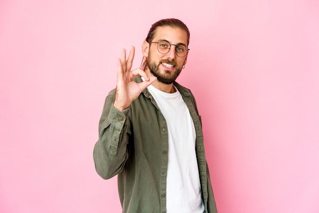 Jonge man met lang haar ziet er vrolijk en zelfverzekerd uit en toont ok gebaar