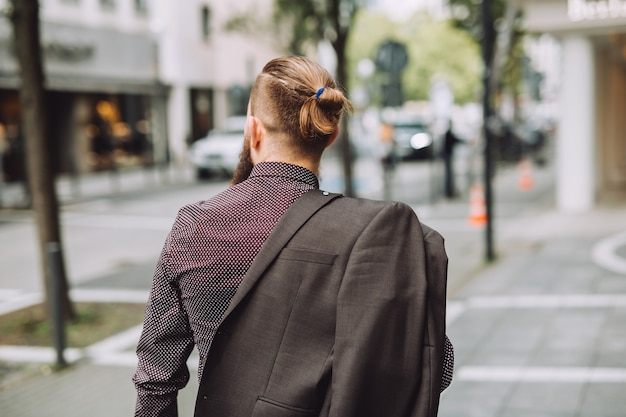 Jonge man met lange baard op de stadsstraat.