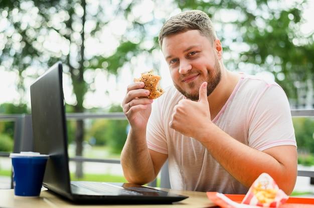 Jonge man met laptop glimlachen op camera