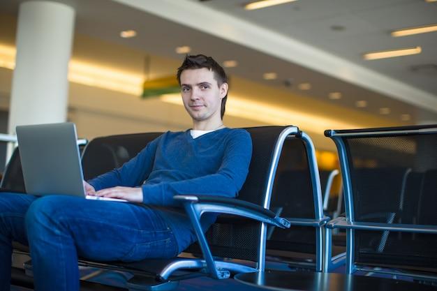 Jonge man met laptop op de luchthaven tijdens het wachten op zijn vlucht
