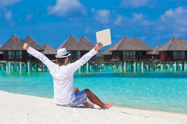 Jonge man met laptop op tropisch strand in de buurt van watervilla