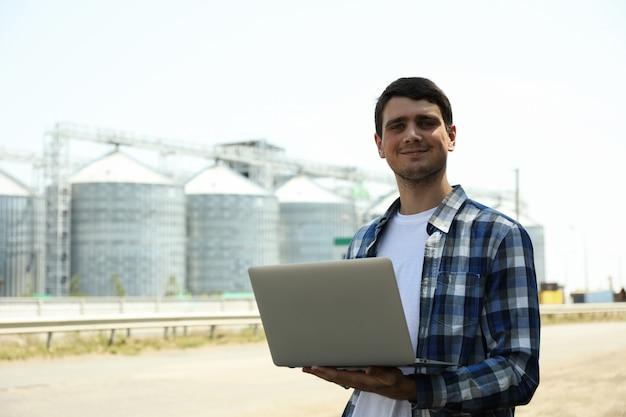 Jonge man met laptop tegen graansilo's. landbouwbedrijf