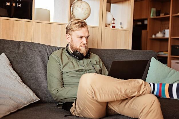 Jonge man met laptop zittend op de bank in de woonkamer. werken in een informele omgeving, op afstand werken, thuiskantoor, freelancer, zelfisolatie, idee van uitstelgedrag
