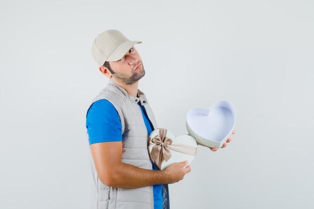 Jonge man met lege geschenkdoos in t-shirt, jasje en peinzend op zoek. vooraanzicht.