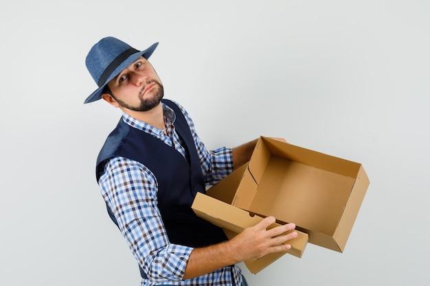 Jonge man met lege kartonnen doos in shirt, vest, hoed en op zoek verdrietig.