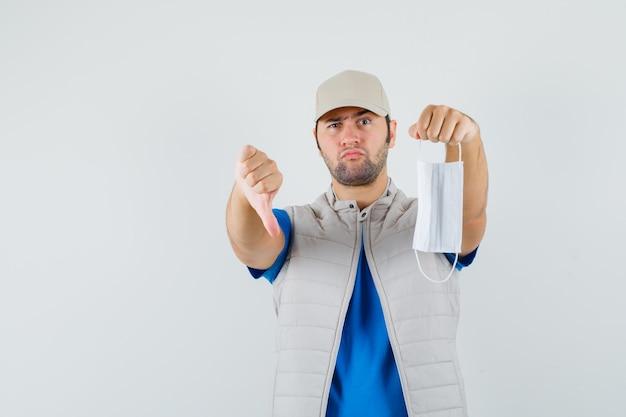 Jonge man met masker, duim omlaag in t-shirt, jasje en op zoek serieus. vooraanzicht.