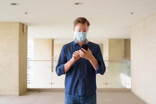Jonge man met masker en gelaatsscherm met behulp van telefoon in modern gebouw