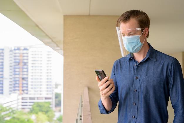 Jonge man met masker en gelaatsscherm met behulp van telefoon met uitzicht op de stad