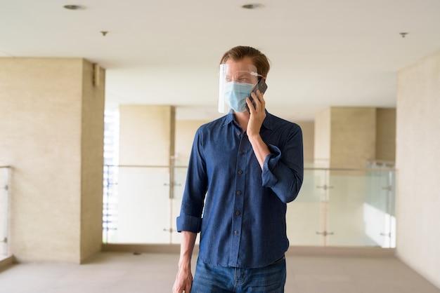 Jonge man met masker en gelaatsscherm praten aan de telefoon in modern gebouw