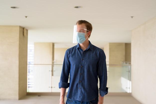 Jonge man met masker en gelaatsscherm voor bescherming tegen uitbraak van coronavirus denken bij modern gebouw