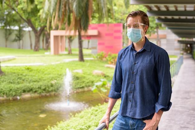 Jonge man met masker en gelaatsscherm voor bescherming tegen uitbraak van coronavirus in het park denken