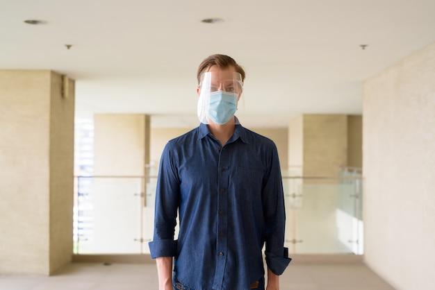 Jonge man met masker en gelaatsscherm voor bescherming tegen uitbraak van coronavirus in modern gebouw