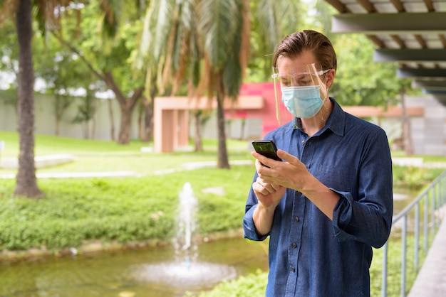 Jonge man met masker en gelaatsscherm voor bescherming tegen uitbraak van coronavirus met behulp van telefoon in het park