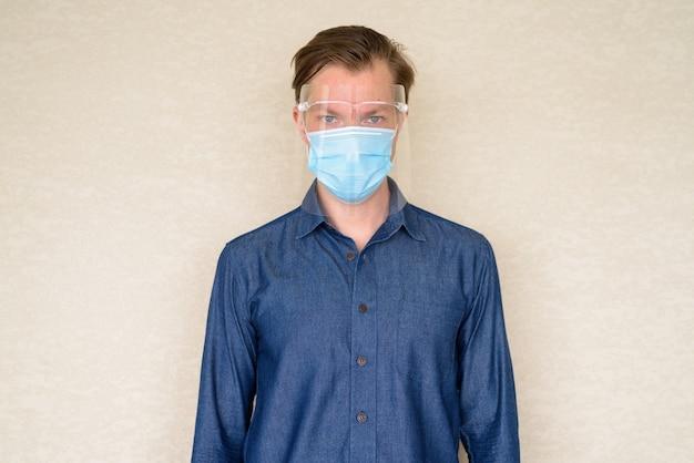 Jonge man met masker en gelaatsscherm voor bescherming tegen uitbraak van coronavirus op betonnen muur