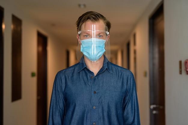 Jonge man met masker en gelaatsscherm voor bescherming tegen uitbraak van het coronavirus in de gang
