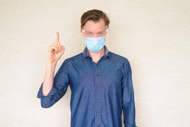 Jonge man met masker en gezichtsscherm die op betonnen muur benadrukt