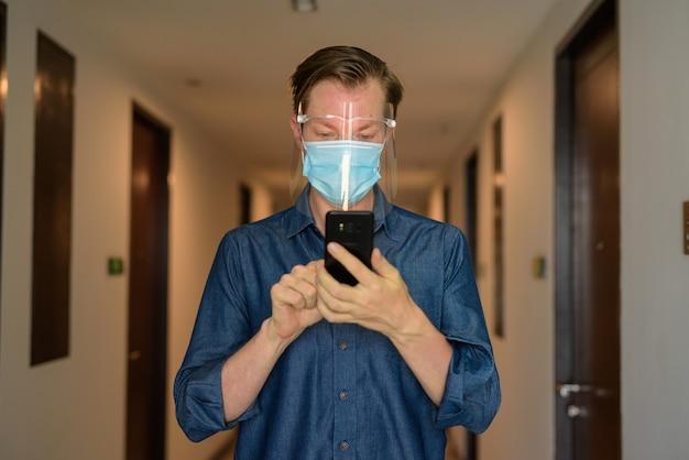 Jonge man met masker en gezichtsscherm met telefoon in de gang