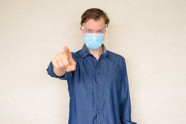 Jonge man met masker en gezichtsscherm naar voren wijzend op betonnen muur