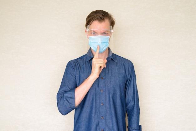 Jonge man met masker en gezichtsschild met vinger op lippen op betonnen muur