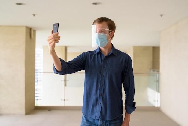 Jonge man met masker en gezichtsschild selfie te nemen bij modern gebouw