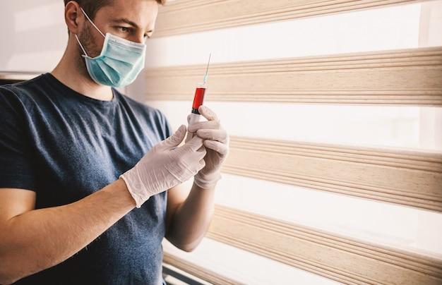 Jonge man met masker en handschoenen kijken naar injectie vol met bloed. wees verantwoordelijk, blijf thuis. wereldpandemie.
