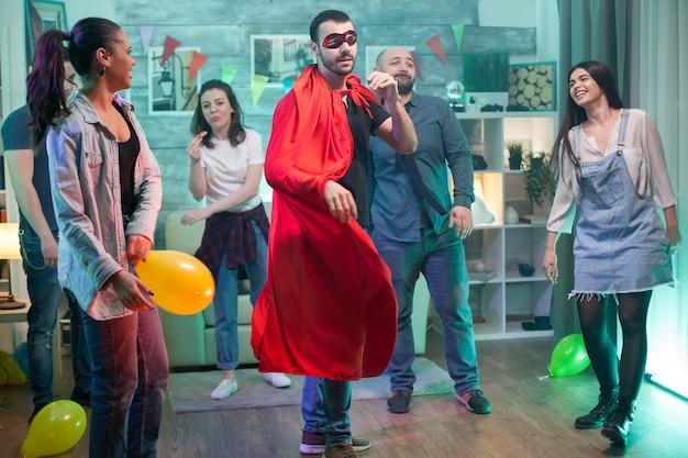 Jonge man met masker en superheld cape die vriendschap viert met een groep mensen.