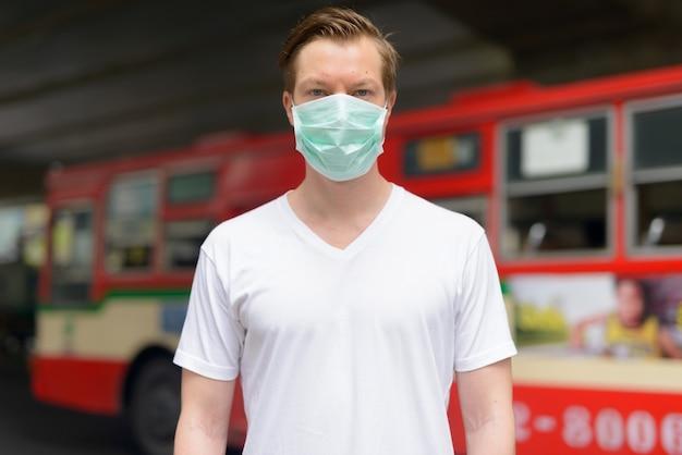 Jonge man met masker in de straten van de stad ter bescherming tegen uitbraak van het coronavirus