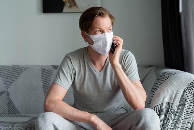 Jonge man met masker praten aan de telefoon thuis in quarantaine