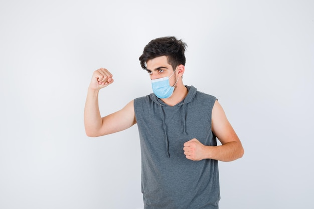 Jonge man met masker terwijl hij spieren toont en vuist in grijs t-shirt balt en er serieus uitziet?