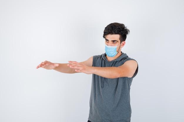 Jonge man met masker terwijl hij zijn handen naar links uitstrekt in grijs t-shirt en er serieus uitziet