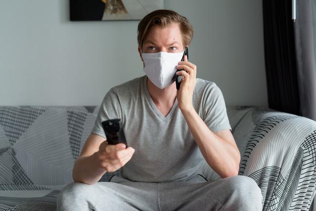Jonge man met masker tv kijken en praten aan de telefoon thuis in quarantaine