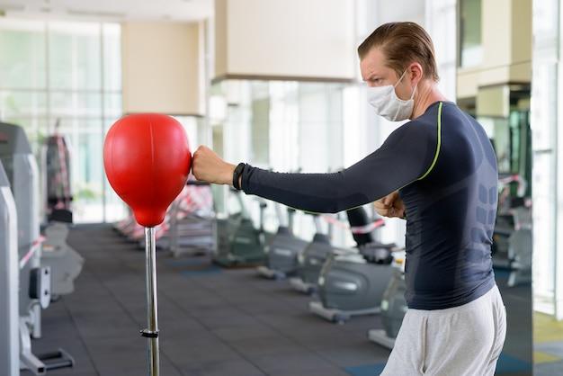 Jonge man met masker voor bescherming tegen coronavirus-uitbraak boksen in sportschool tijdens coronavirus covid-19
