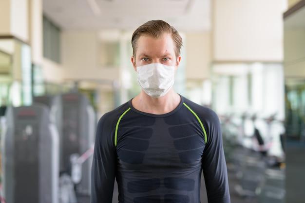 Jonge man met masker voor bescherming tegen uitbraak van coronavirus in sportschool tijdens coronavirus covid-19