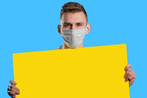 Jonge man met medisch masker geel papier poster tonen en camera kijken op blauwe achtergrond. reclame concept