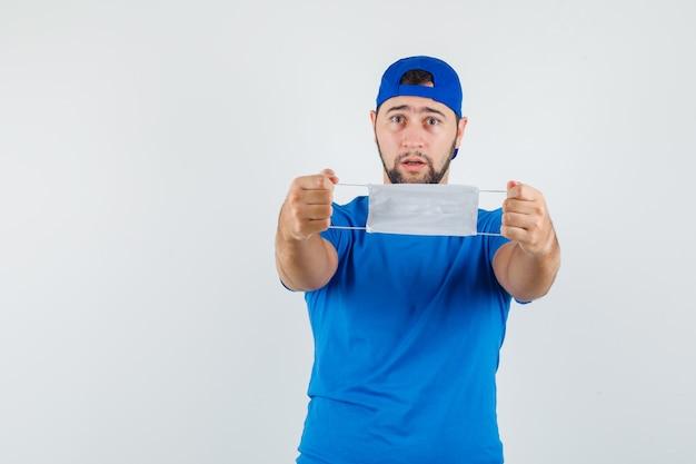 Jonge man met medisch masker in blauw t-shirt en pet en voorzichtig kijken